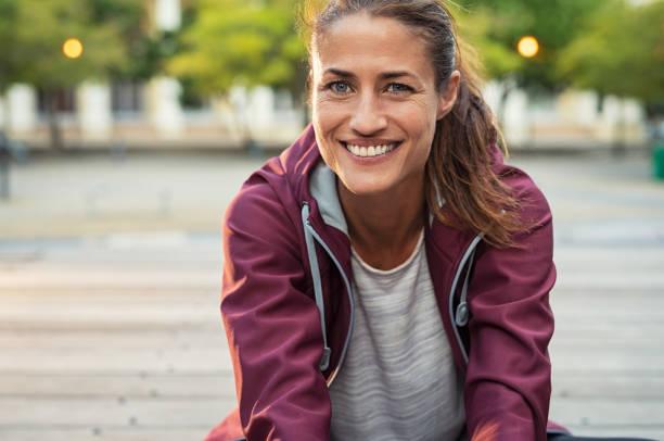 lächelnde sportliche milf - joggerin stock-fotos und bilder