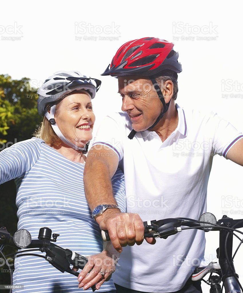 Smiling mature woman and husband riding bicycles royalty-free stock photo