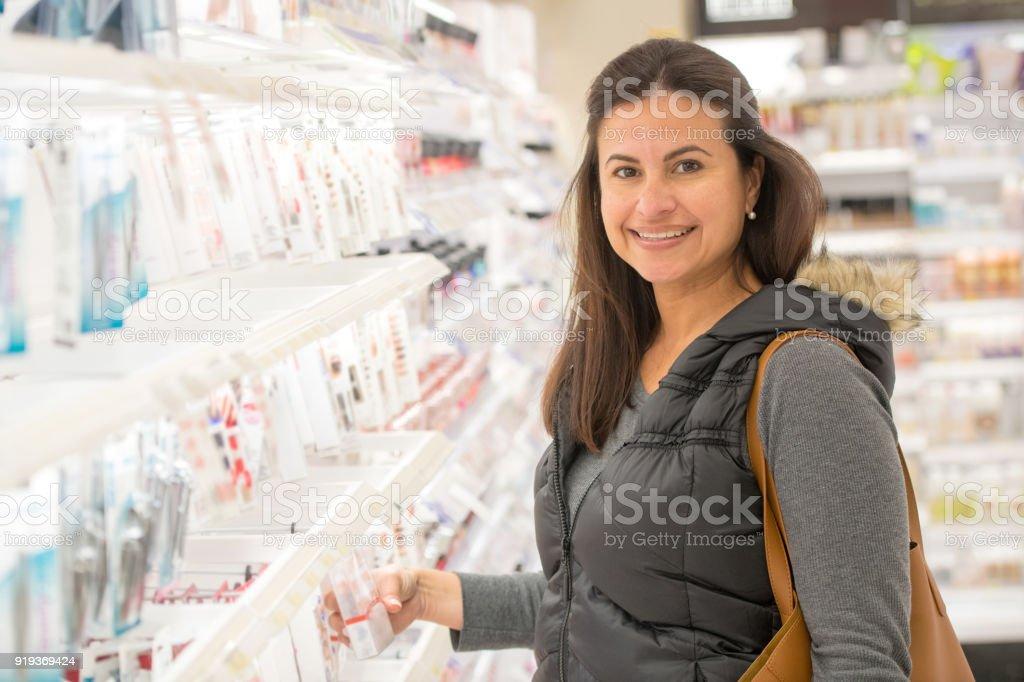 Mulher madura em uma loja de produtos de beleza a sorrir - foto de acervo