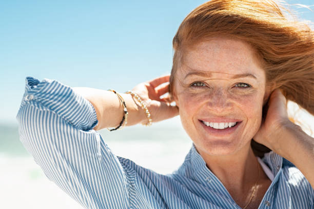 smiling mature woman at beach - donna foto e immagini stock