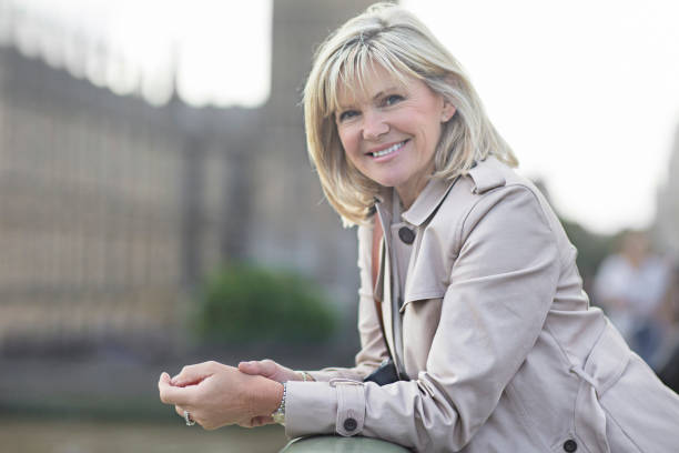 smiling mature woman at westminster bridge - medium length hair stock photos and pictures