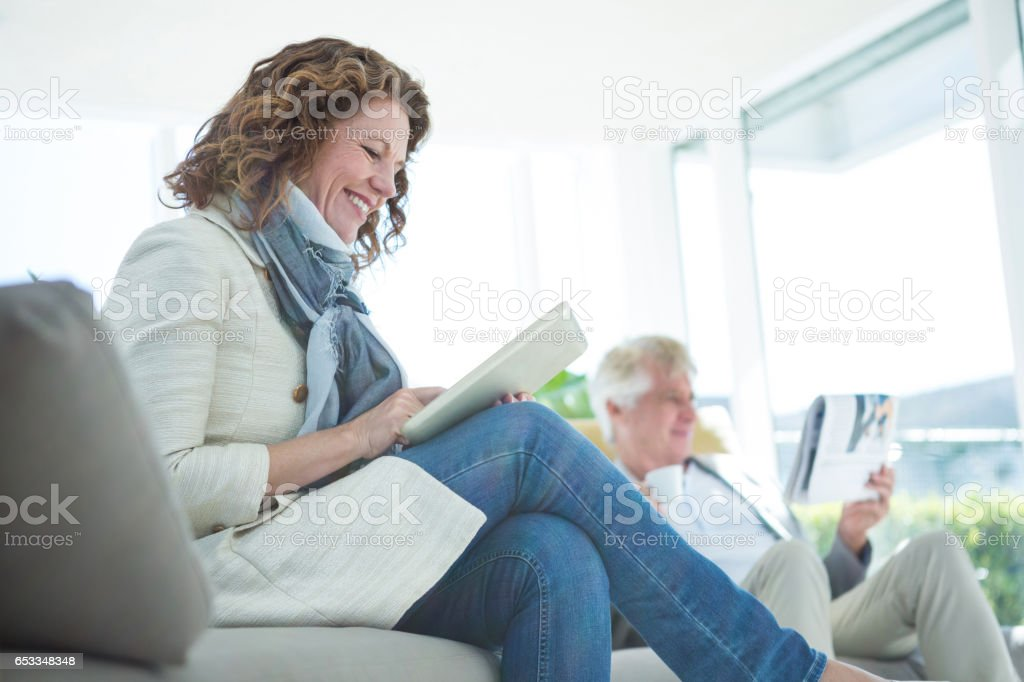 Smiling mature woman by man using digital tablet stock photo