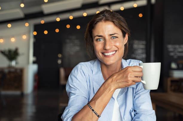 reife frau kaffee trinken lächelnd - gesichtertassen stock-fotos und bilder