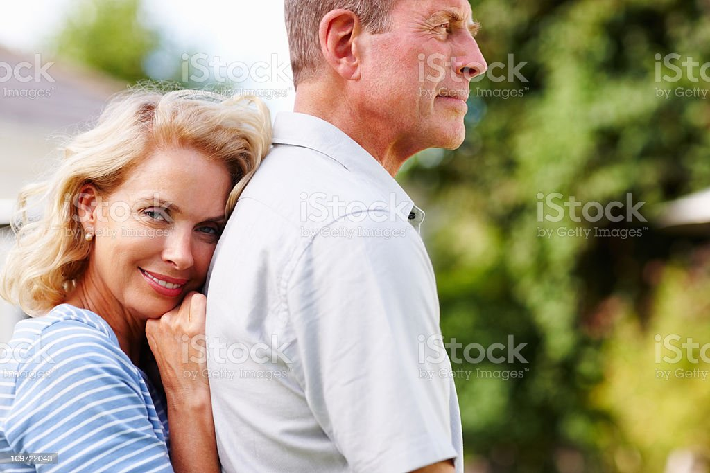 Smiling mature woman embraces senior man from back royalty-free stock photo