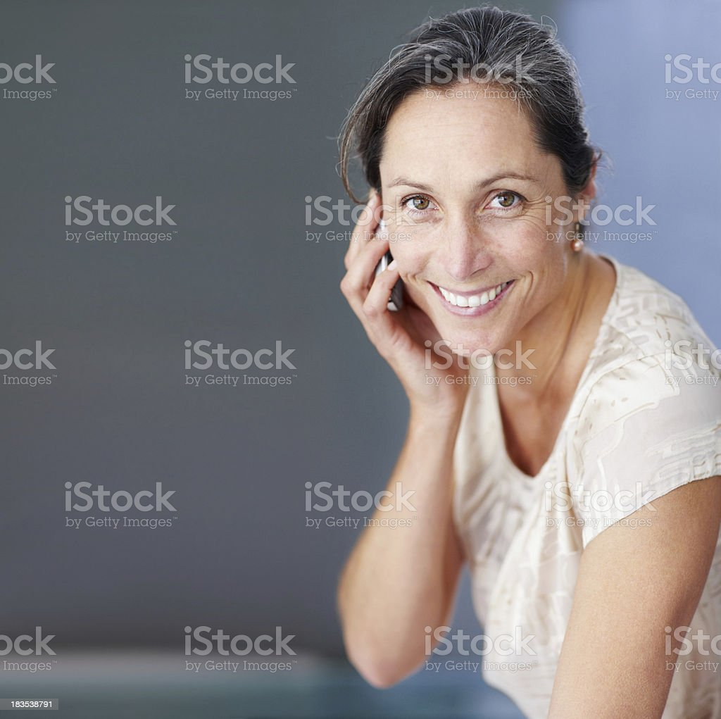 Smiling mature woman having a conversation on cellphone royalty-free stock photo