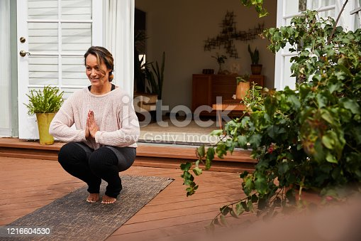 Mature woman in sportswear smiling while practicing yoga alone outside on her patio