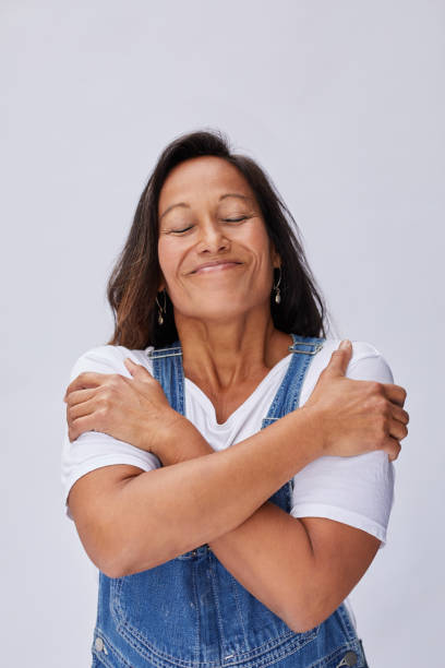 Smiling mature woman hugging herself with her eyes closed stock photo