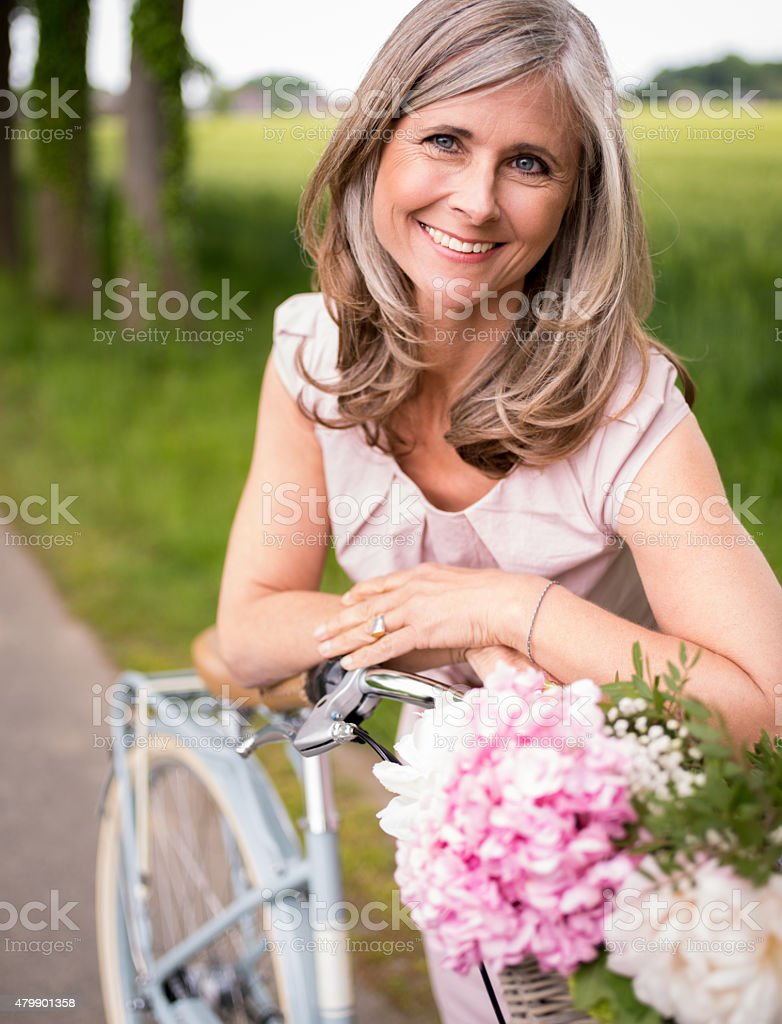Smiling mature woman in a park with her bicycle stock photo