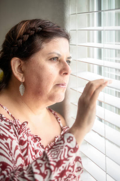 Smiling mature woman looking through a window Smiling hispanic or middle eastern woman looking looking through a window deportation stock pictures, royalty-free photos & images