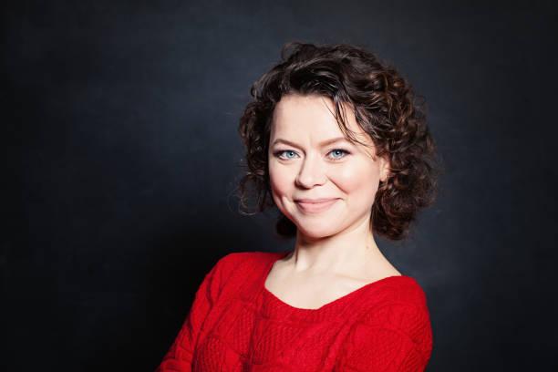 smiling mature woman on blackboard background. mature beauty - 파마 뉴스 사진 이미지