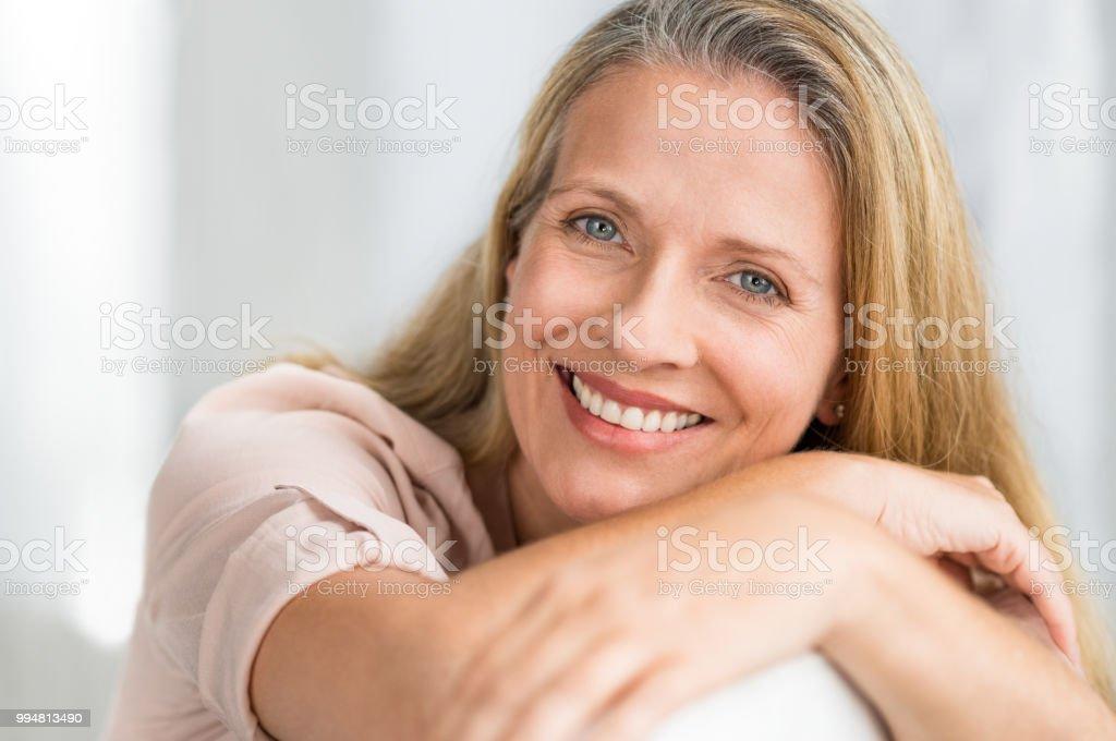 Femme mûre souriante sur canapé - Photo