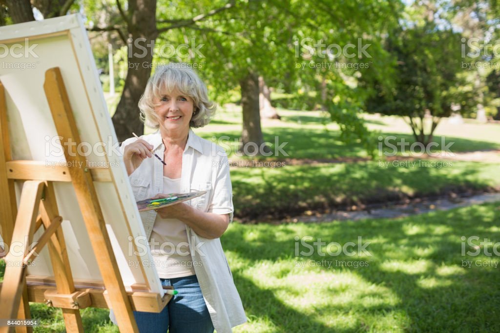 Smiling mature woman painting in park stock photo