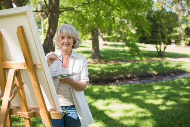 smiling mature woman painting in park - active seniors stock photos and pictures
