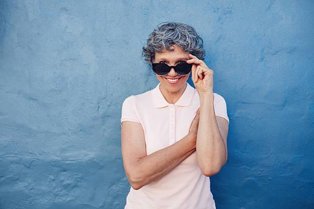 Smiling mature woman peeking over sunglasses stock photo