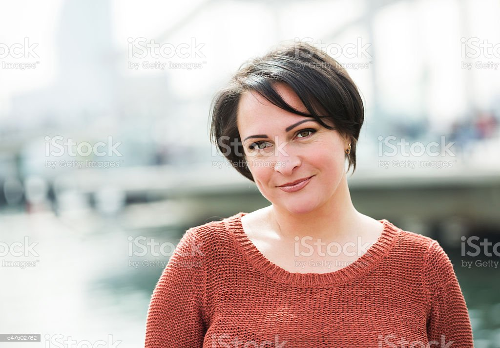 Smiling  mature woman posing outdoors stock photo