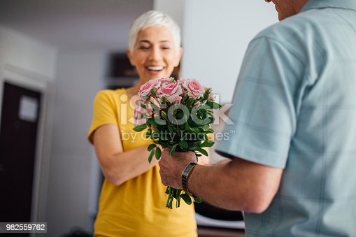 istock Smiling mature woman receiving flowers from her husband 982559762