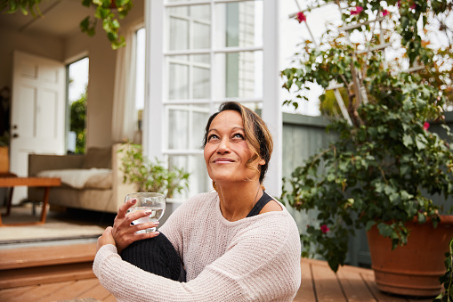 Mature woman smiling while sitting alone on her patio outside drinking a glass of water