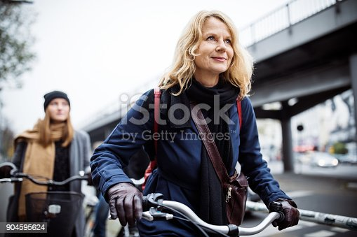 Smiling mature woman riding bicycle. Friends traveling together in city. They are in warm clothing.