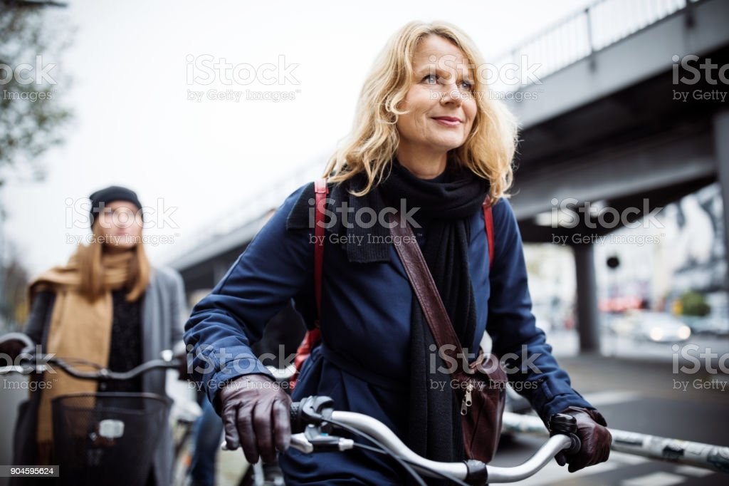 Smiling mature woman riding bicycle with friend stock photo