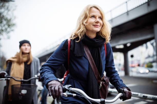 lächelnd reife frau reiten fahrrad mit freund - alvarez stock-fotos und bilder