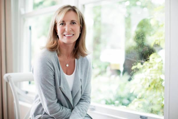 rijpe vrouw door raam thuis zitten glimlachen - 50 54 jaar stockfoto's en -beelden