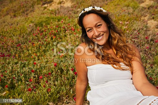 istock Smiling mature woman sitting in a field of wildflowers 1217525806