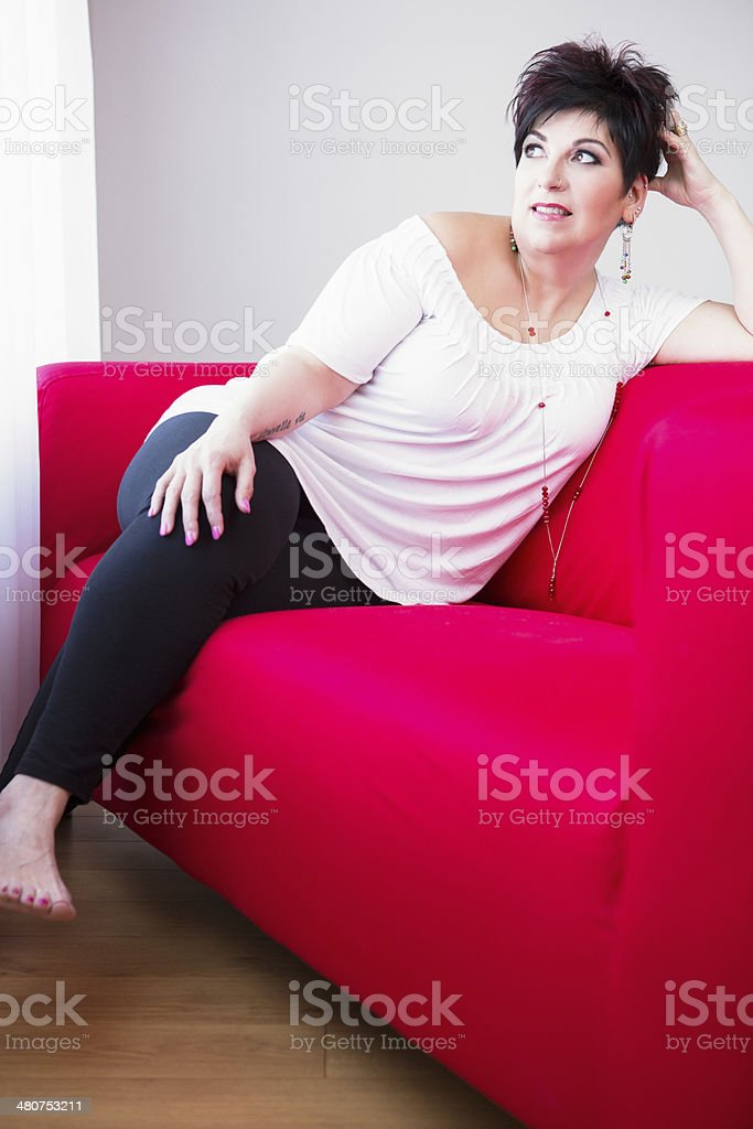 Smiling mature woman sitting on couch royalty-free stock photo