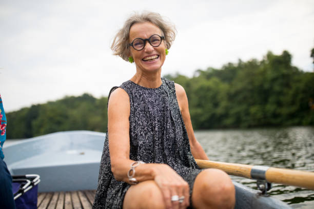 smiling mature woman sitting on rowboat in lake - woman portrait forest foto e immagini stock