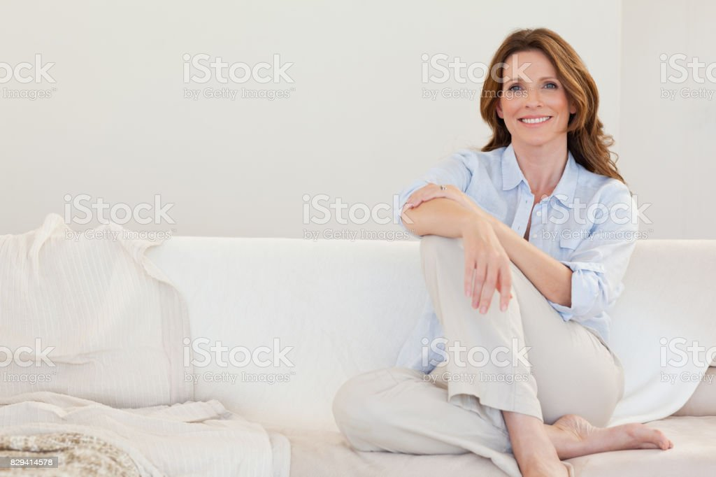 Smiling mature woman sitting on sofa stock photo