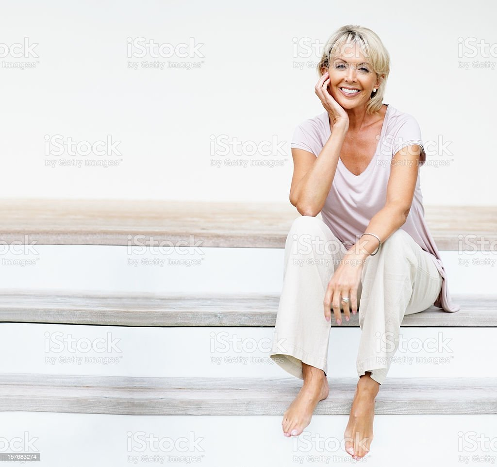 Smiling mature woman sitting on staircase - copyspace royalty-free stock photo