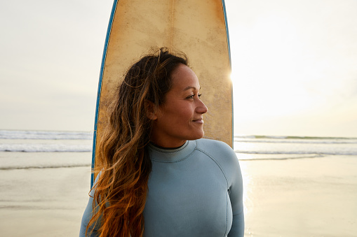 Smiling mature woman in a wetsuit standing with her surfboard on a beach in the late afternoon