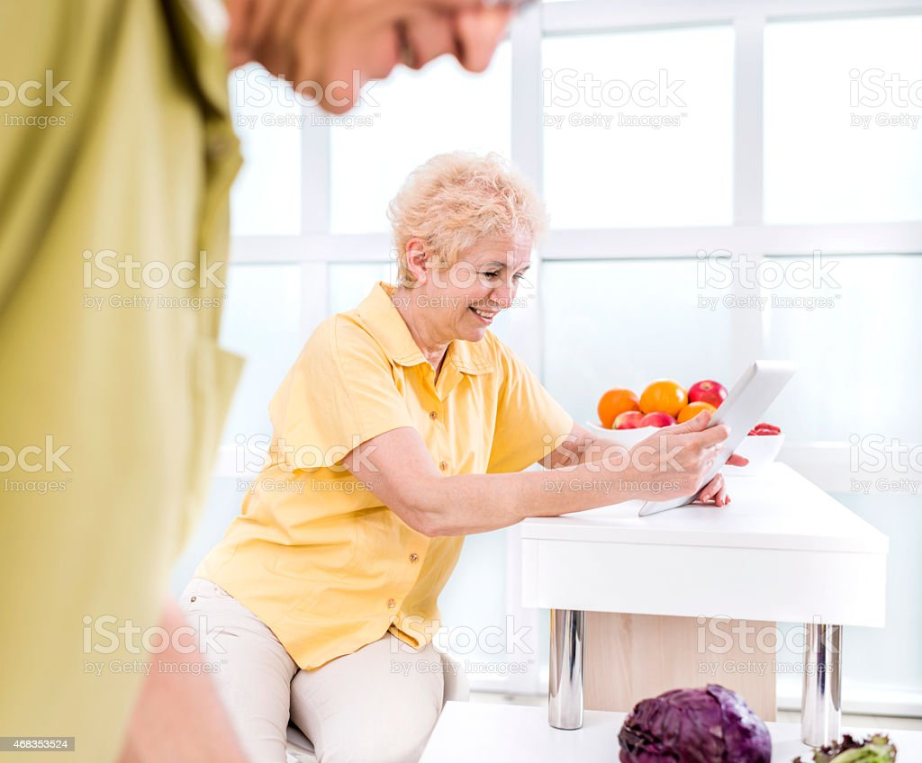 Smiling mature woman using digital tablet in the kitchen. royalty-free stock photo