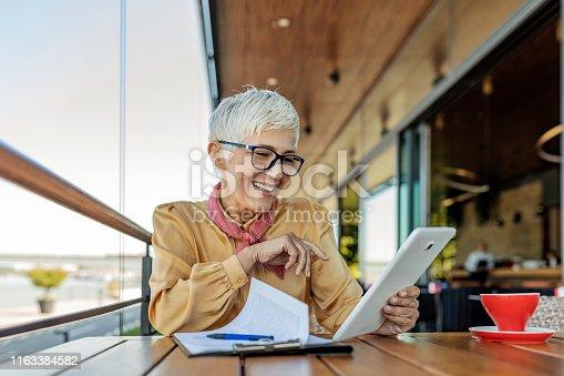 Mature business woman at cafe using Tablet. Senior woman wearing eyeglasses reading on digital tablet. Female at cafe using digital tablet.