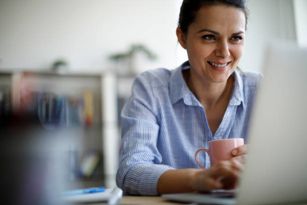 Smiling mature woman using laptop for working at home stock photo