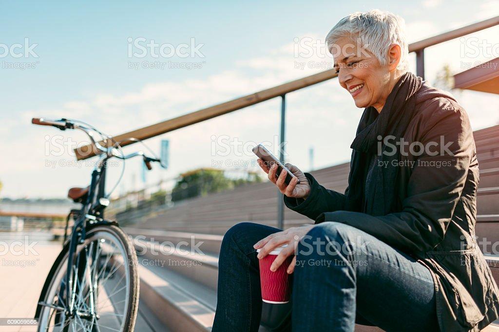Smiling Mature Woman Using Smart Phone. stock photo