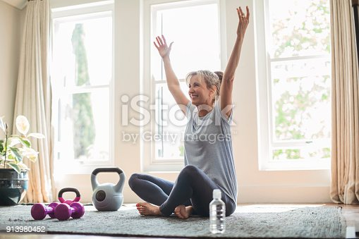 istock Smiling mature woman with hands raised doing yoga 913980452