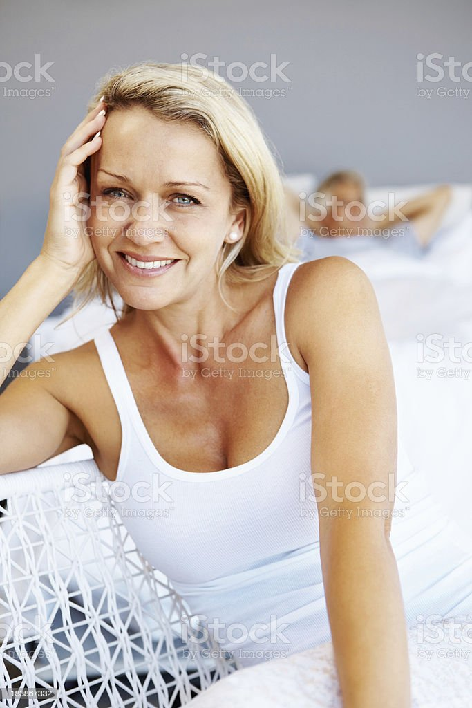 Smiling, mature woman with man lying in bed royalty-free stock photo