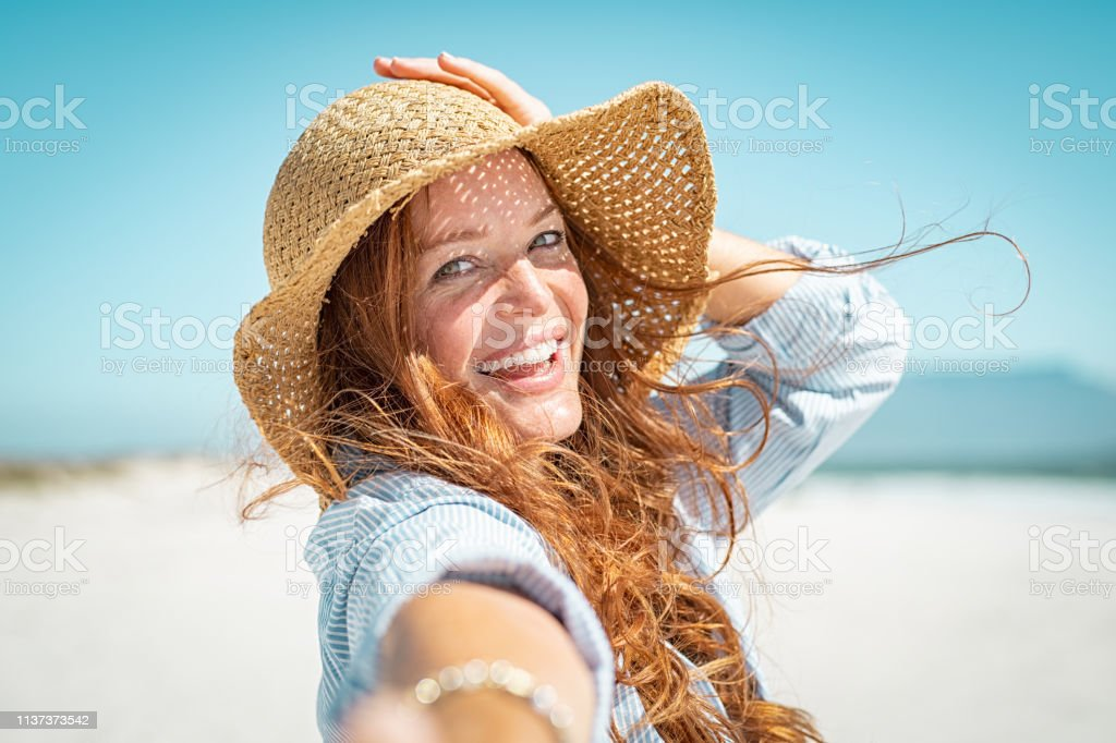 Smiling mature woman with straw hat Portrait of beautiful mature woman in casual wearing straw hat in sunny warm day at seaside. Cheerful young woman smiling at beach during summer vacation. Happy girl with red hair and freckles enjoying the sun. Adult Stock Photo