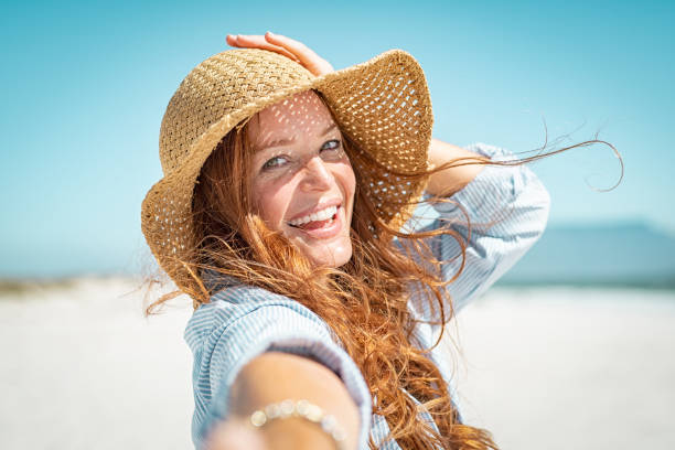 Smiling mature woman with straw hat Portrait of beautiful mature woman in casual wearing straw hat in sunny warm day at seaside.Cheerful young woman smiling at beach during summer vacation. Happy girl with red hair and freckles enjoying the sun. one mature woman only stock pictures, royalty-free photos & images