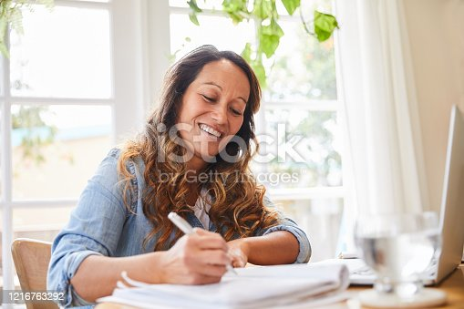 Smiling mature woman writing down ideas in a notebook while working at a table in her living room at home
