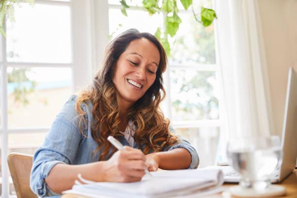 улыбающаяся зрелая женщина, пишущая в блокноте во время работы из дома - писать стоковые фото и изображения