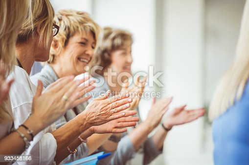 1028234706 istock photo Smiling mature women clapping hands during seminar 933458166