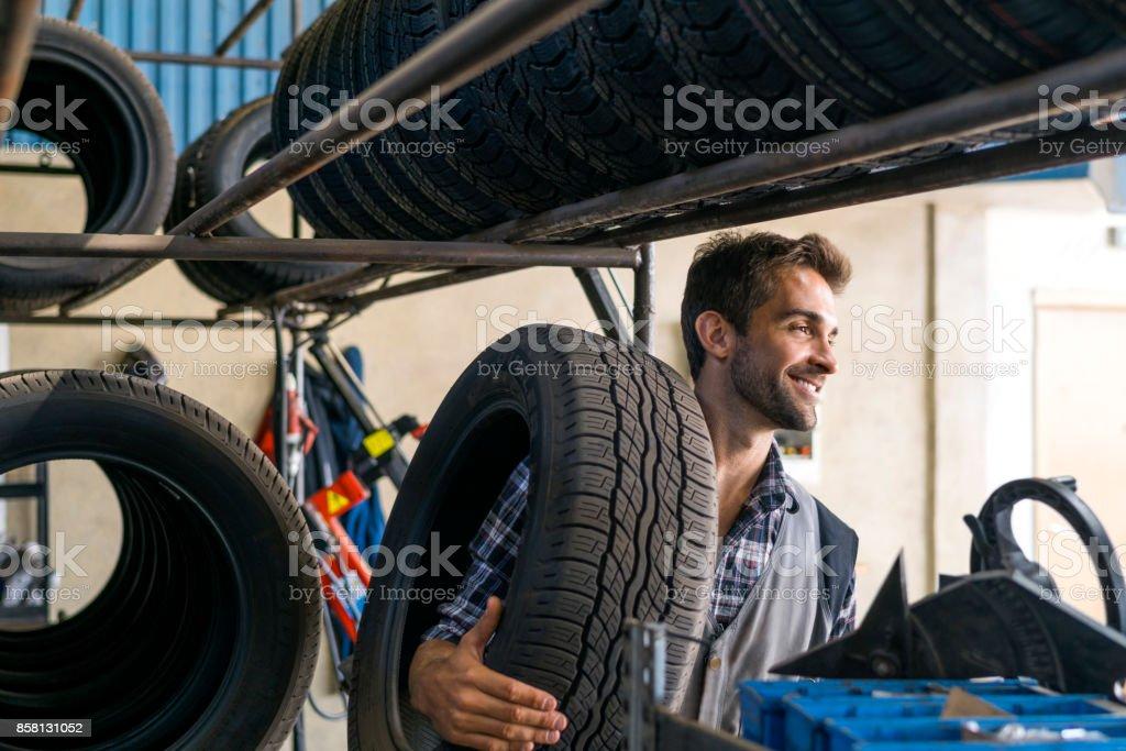 Lächelnde Mechaniker bei Autowerkstatt Reifen tragen – Foto