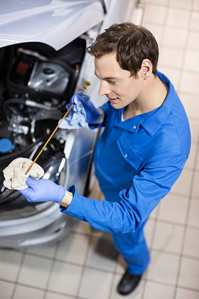 Smiling mechanic checking oil with dipstick next to car stock photo