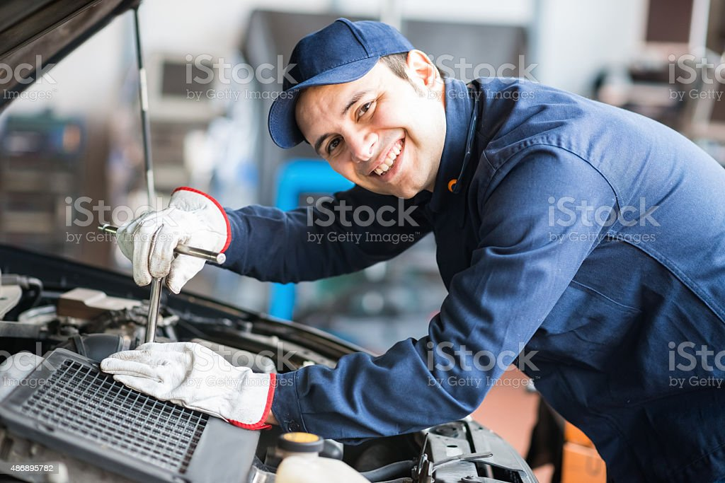 Smiling mechanic fixing a car engine stock photo