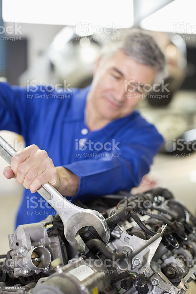 Smiling mechanic fixing engine with large wrench in auto repair shop royalty-free stock photo