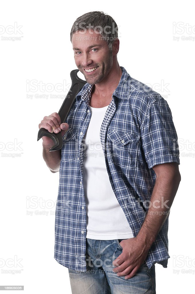 smiling mechanic holding a wrench royalty-free stock photo