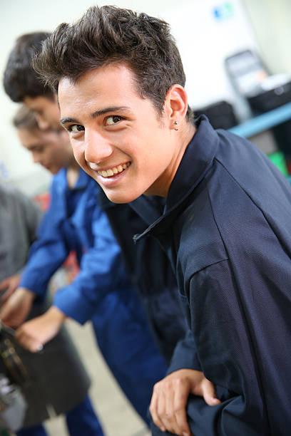 Smiling mechanic in auto garage stock photo