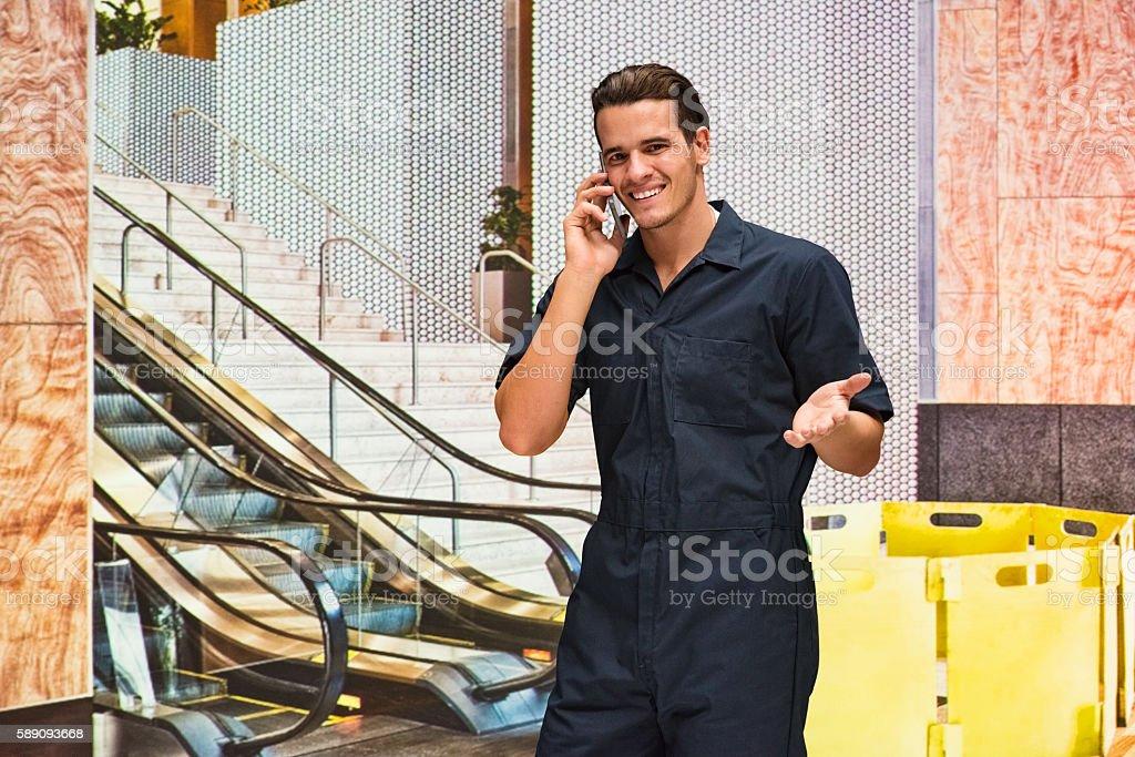 Smiling mechanic talking on phone stock photo