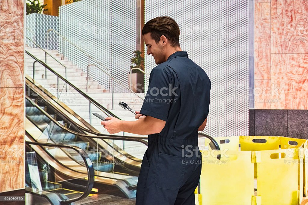 Smiling mechanic using phone in office stock photo